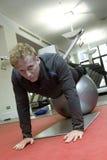 Persoonlijke trainer die opdrukoefeningen op Zwitserse bal doet Stock Fotografie