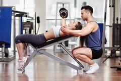 Persoonlijke trainer die vrouw helpt bij gymnastiek royalty-vrije stock foto's