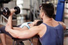 Persoonlijke trainer die vrouw helpt bij gymnastiek Stock Afbeelding