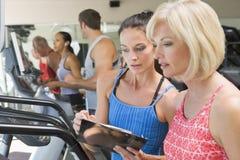 Persoonlijke Trainer die Vrouw op Tredmolen instrueert Royalty-vrije Stock Foto