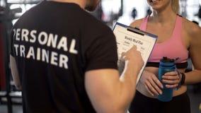 Persoonlijke trainer die wekelijks maaltijdplan bespreken met vrouwelijke cliënt in gymnastiek, steun royalty-vrije stock fotografie