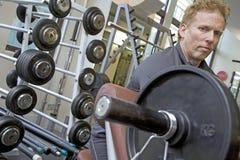 Persoonlijke trainer werkende bicepsen op een bank Stock Foto