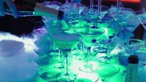 Persoons gietende champagne aan piramide van glazen stock video
