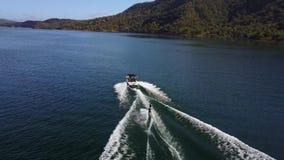 Persoons het water die maakte aan motorboot vast in het tropische oceaanzeegezicht van de berghorizon in schitterende 4k luchthom stock video
