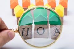 Persoons` s Hand die de Houten Blokken van de Huiseigenaarvereniging onderzoeken stock afbeeldingen