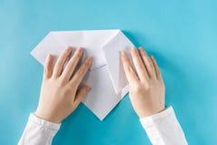 Persoons` s handen die een document vliegtuig vouwen stock afbeelding