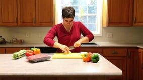 Persoons scherpe uien in hun keuken stock footage