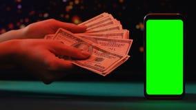 Persoons tellende dollars dichtbij smartphone met het groene scherm, online leningen, krediet stock footage