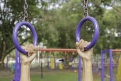 Persoonsgreep het blauw die het openluchtoefeningsmateriaal in openbaar park hangen Stock Fotografie