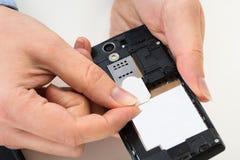 Persoonshand met simkaart en mobiele telefoon Stock Afbeeldingen