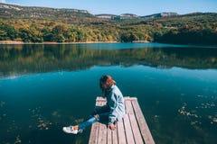 Persoonszitting op edele door het meer stock foto