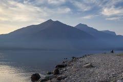 Persoonszitting op kust van meer met berg op achtergrond stock foto