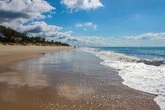 Perspectief die van nat strand op blauwe bewolkte hemel met golven wijzen die binnen en sihlouttes van mensen die naar de horizon stock afbeelding