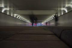 Perspectief van een ondergrondse tunnel met silhouetten van mensen die langs lopen royalty-vrije stock afbeeldingen
