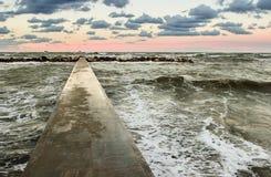 Perspectiefmening van een concrete pijler bij het overzees bij zonsondergang Royalty-vrije Stock Foto's