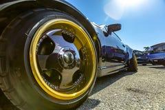 Perspectiefmening van een zwarte auto met grote gouden randen in Fr stock foto