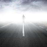 Perspectiva da estrada do asfalto com homem de passeio imagem de stock royalty free
