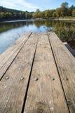 Perspectiva da tabela de piquenique de madeira com fundo do vertical da paisagem do borrão imagens de stock
