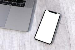 Perspectiva de la maqueta del smartphone del estilo de la plata de IPhone Xs en la tabla imágenes de archivo libres de regalías