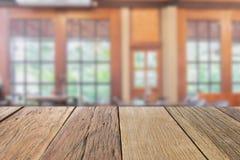 Perspectiva de madeira vazia do tampo da mesa com o backgro da cafetaria do borrão fotos de stock