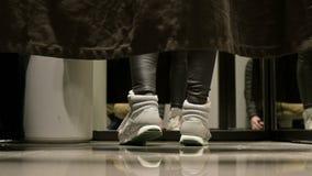 Perspectiva del nivel del piso Detrás de la cortina en el probador de una tienda, las piernas de las mujeres en zapatos de los de metrajes