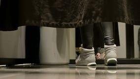 Perspectiva del nivel del piso Detrás de la cortina en el probador de una tienda, las piernas de las mujeres en zapatos de los de almacen de video