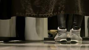 Perspectiva del nivel del piso Detrás de la cortina en el probador de una tienda, las piernas de las mujeres en zapatos de los de almacen de metraje de vídeo