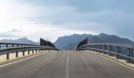 Perspectiva del puente del camino contra las montañas imagen de archivo