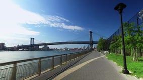 Perspectiva do ` s do cavaleiro que Biking em East River Bikeway perto da ponte de Williamsburg video estoque