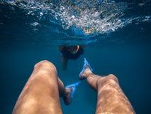 Perspectiva personal de una natación masculina al revés subacuática Mujer joven que sigue a su novio foto de archivo