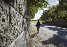 Perspectiva profunda a lo largo de una pared de piedra y de un hombre que caminan en una calle del otoño Imagen de archivo libre de regalías