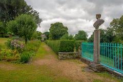 Perspectiva que lleva al orangerie con el busto romano, jardín de Plas Brondanw, País de Gales del norte fotos de archivo