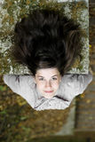 Perspective on beautiful hair. Young attractive girl lying on a concrete wall Royalty Free Stock Photos