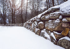Perspective of beautiful old stone wall, with a misty winter forest in the background. Stock Photo