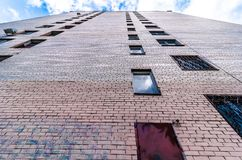 Perspective of brick tall building of residential flats and apartments. View on a brick apartment building from down to up. Perspective of brick tall house royalty free stock images