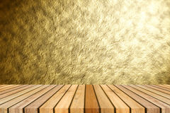 Perspective brown wooden floor against Abstract gold texture background with beautiful spotlight emit effect. Royalty Free Stock Photo