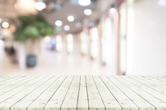 Perspective empty white wooden table over blurred shopping mall Stock Image