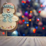 A gingerbread snowman on a wooden table against decorated Christmas tree stock photos
