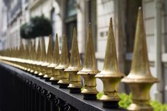 Close up of golden painted iron fence spikes. Perspective horizontal view of golden painted iron fence spikes surrounding a residential property stock photo