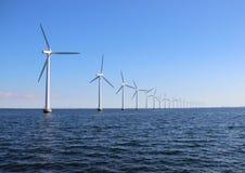 Perspective line of ocean wind mills with dark water and sky. Perspective line of ocean wind mills with dark water and light blue sky royalty free stock photo