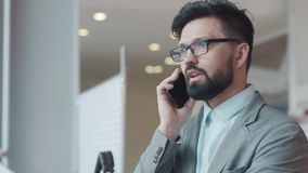 Perspective man with a briefcase has a business phone call. Portrait. Attractive young man in gray suit, with glasses and beard, answers the phone, communicates stock video