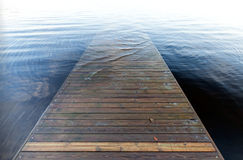 Perspective of an old wooden pier goes under water Stock Photography