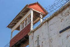 Prison guard tower. Perspective of a prison guard tower from below. Old flaking paint on the wall and barbed wire on top of the wall stock photos