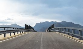 Perspective of road bridge against mountains stock image