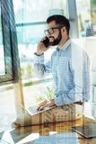 Perspective satisfied employer sitting and having conversation. Best gadgets. Perspective joyful satisfied employer sitting in the room on the table using the Royalty Free Stock Photos