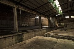 Shed in abandoned factory. Perspective shed in abandoned factory, with visible rusty metal barrels and debries Stock Images