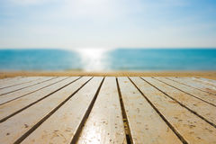 Perspective table on the beach with bright blue sea, blurred. royalty free stock photography