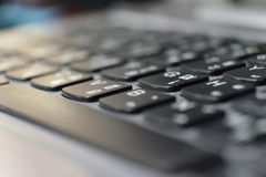 Perspective of the thai keyboard of a laptop in black blur Stock Photos