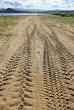 Perspective of tyre tracks on sandy beach Stock Image