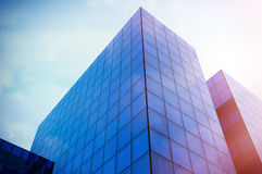 Perspective and underside angle view to textured background of modern glass blue building skyscrapers. Sunset light Stock Photography